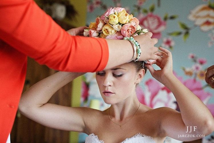 Wianek ślubny z żywych ciętych kwiatów na głowie Pani Młodej.