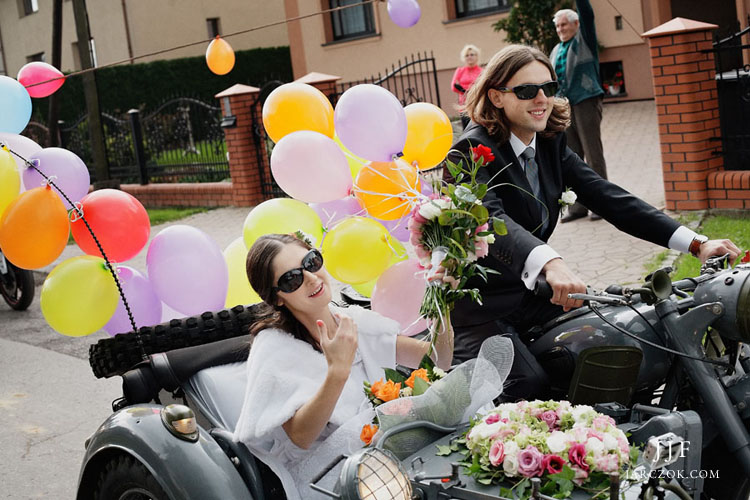Państwo młodzi jadą do ślubu motocyklem z boczną przyczepą.